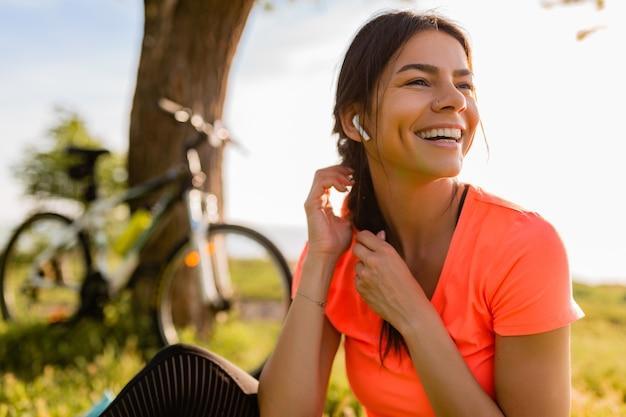 Retrato de mulher bonita sorridente fazendo esportes de manhã no parque