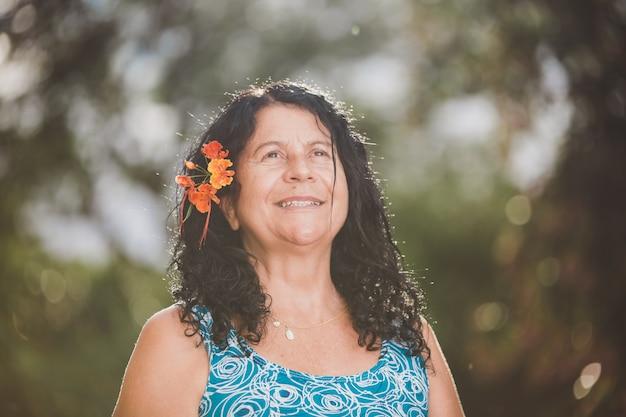 Retrato de mulher bonita sorridente na natureza com flores no cabelo