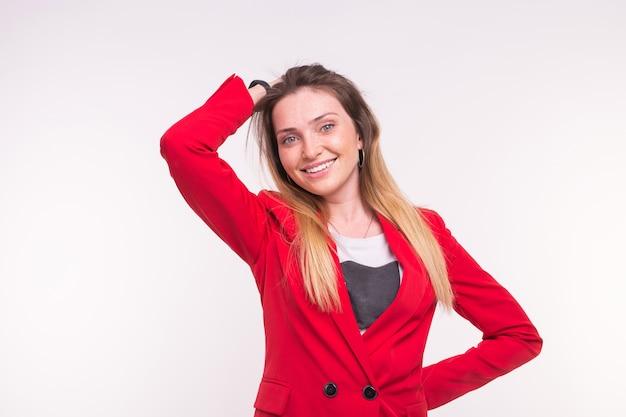 Retrato de mulher bonita sorridente sardento vestindo terno vermelho sobre fundo branco.