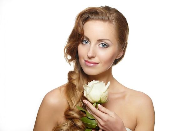 Retrato de mulher bonita sorridente sensual com rosa branca no branco