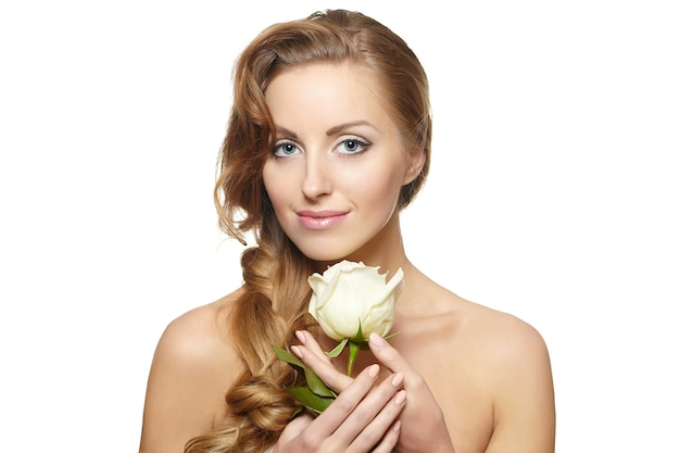 Retrato de mulher bonita sorridente sensual com rosa branca sobre fundo branco, cabelo encaracolado, maquiagem brilhante