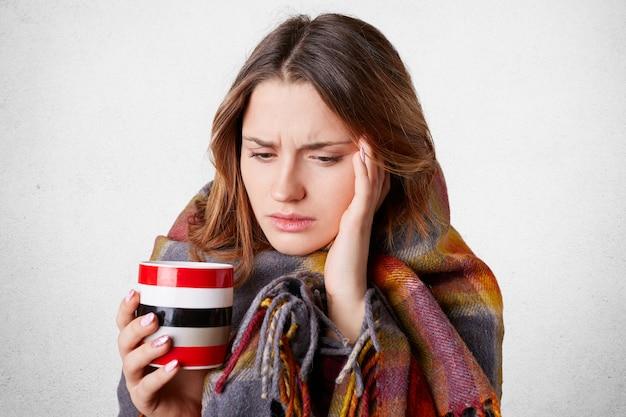 Retrato de mulher bonita tem dor de cabeça, tem frio, bebe chá ou café quente, embrulhado no cobertor xadrez, parece miserável, isolado sobre o concreto branco