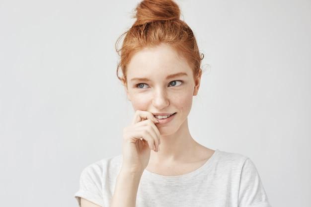 Retrato de mulher bonita tímida com cabelo sexy e sardas sorrindo.