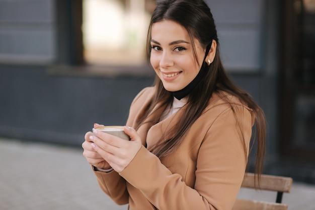 Retrato de mulher bonita tira a máscara protetora para beber café. mulher sentada ao ar livre no terraço e bebe café.