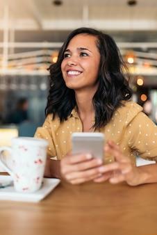 Retrato de mulher bonita usando celular na cafeteria.