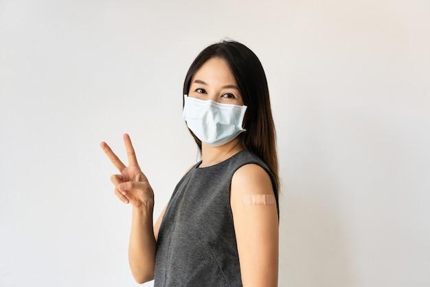 Retrato de mulher bonita usando máscara cirúrgica, sorrindo com uma cara feliz para a câmera, fazendo sinal de vitória. mulher asiática apontando dois dedos após receber a segunda dose da vacina covid-19. copie o espaço.