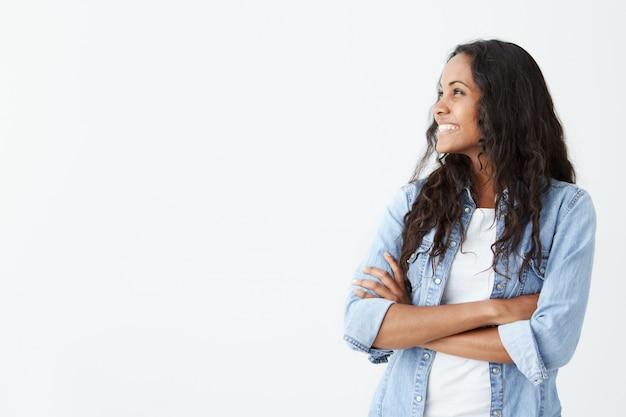 Retrato de mulher bonita vestida de camisa jeans jovem com pele escura, tendo expressão alegre, olhando alegremente para longe, segurando os braços cruzados.
