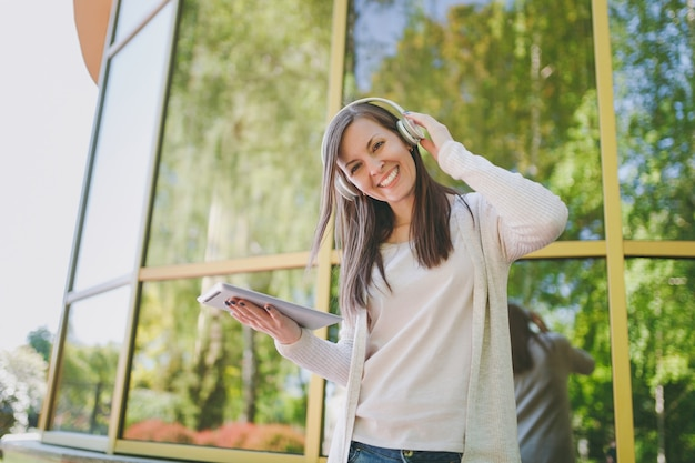 Retrato de mulher bonita, vestindo roupas leves casuais. menina segurando o computador tablet pc, ouvindo música em fones de ouvido no parque da cidade, perto do espelho, construindo ao ar livre na natureza da primavera. conceito de estilo de vida.