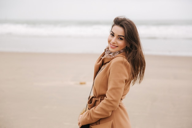Retrato de mulher bonita walkink ao longo da costa, perto do mar do norte. senhora elegante com casaco marrom
