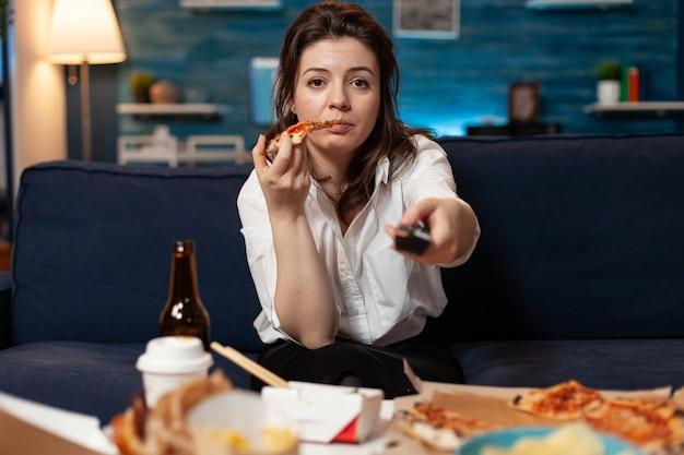 Retrato de mulher branca sentada no sofá, comendo uma fatia de pizza, desfrutando de comida para viagem para casa