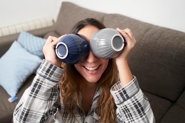 Retrato de mulher brincando. ela está de pijama em casa brincando com 2 xícaras de café.