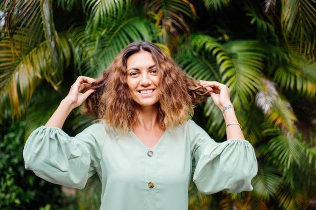 Retrato de mulher bronzeada europeia sorridente feliz com cabelo curto e encaracolado em vestido romântico de manga comprida de verão fora da villa