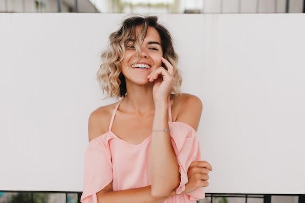 Retrato de mulher bronzeada sensual, tocando seu cabelo ondulado claro. excitada moça bonita em traje de verão rosa.