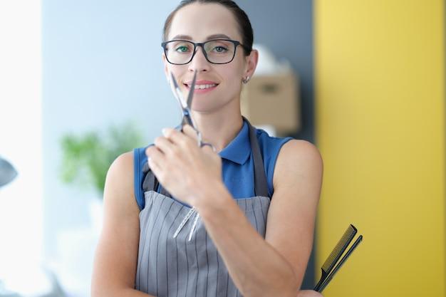 Retrato de mulher cabeleireira com avental segurando uma tesoura closeup