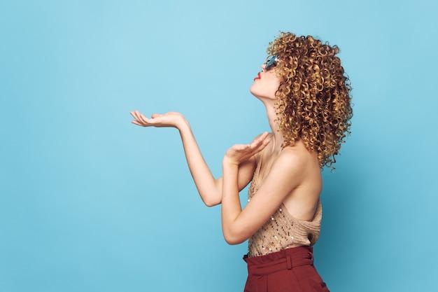 Retrato de mulher, cabelo cacheado, gesto de modelo com charme de mãos e parede isolada