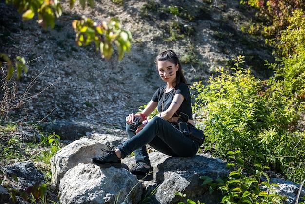 Retrato de mulher caçadora em top curto com arma olhando para longe na natureza