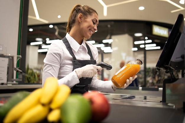 Retrato de mulher caixa em supermercado lendo código de barras de produtos à venda