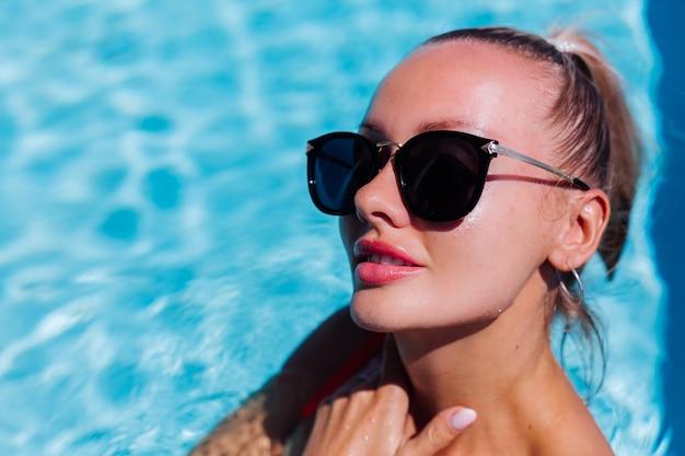 Retrato de mulher calma e feliz em óculos de sol com pele bronzeada em piscina azul em dia de sol