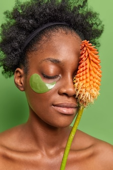 Retrato de mulher calma faz tratamentos anti-rugas em casa usa cosméticos modernos produtos de beleza feitos de ingredientes naturais usa adesivos de hidrogel sob os olhos fica sem camisa.