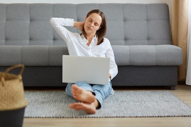 Retrato de mulher cansada, blogueira ou freelancer, vestindo jeans e camisa branca, mulher trabalhando muitas horas, tendo uma dor terrível no pescoço, massageando os músculos, mantendo os olhos fechados.