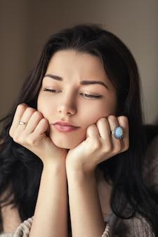 Retrato de mulher cansada com olhos vazios e entediados. modelo asiático caucasiano de raça mista dentro de casa