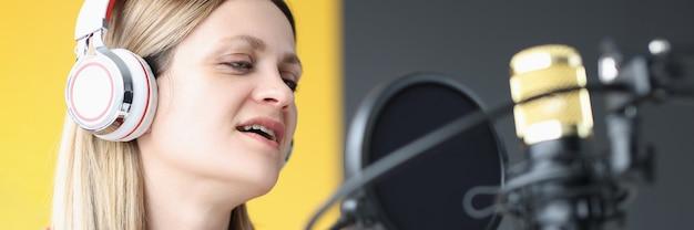 Retrato de mulher cantando em fones de ouvido na frente do microfone, paixão por canto e voz