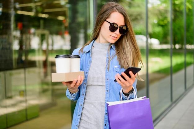 Retrato de mulher carregando café e sacolas de compras