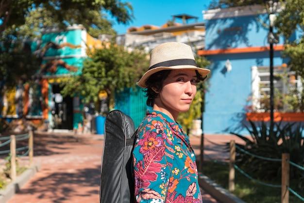 Retrato de mulher carregando um violão com seu estojo no parque