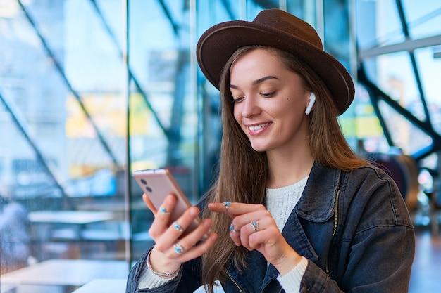 Retrato de mulher casual de moda hipster de moda no chapéu com fones de ouvido sem fio e telefone celular em um café. estilo de vida digital e pessoas modernas