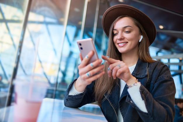 Retrato de mulher casual elegante hipster feliz na moda no chapéu com fones de ouvido sem fio e telefone celular em um café. pessoas modernas com estilo de vida digital