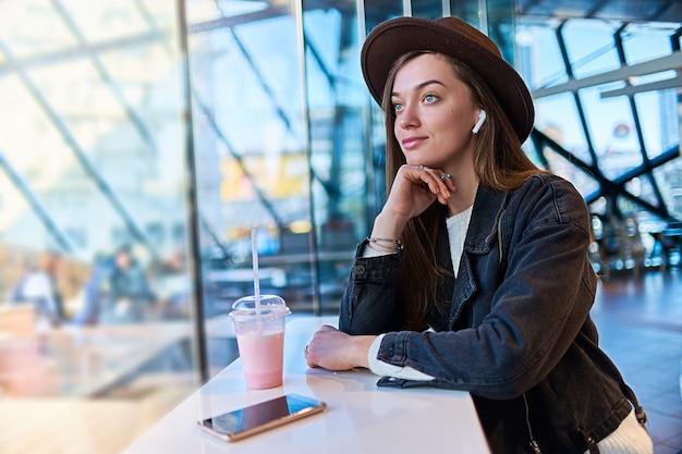 Retrato de mulher casual na moda hipster atraente elegante no chapéu com fones de ouvido sem fio no café. pessoas modernas com estilo de vida digital de tecnologia