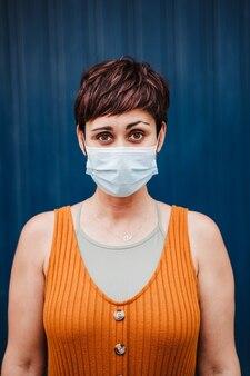 Retrato de mulher caucasiana ao ar livre, usando máscara facial. conceito de distância social. pandemia durante o vírus corona
