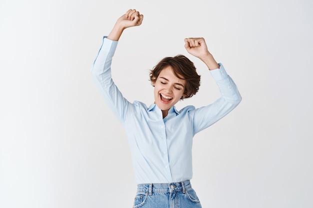 Retrato de mulher caucasiana feliz dançando e se divertindo, sorrindo despreocupada, se divertindo, em pé na parede branca