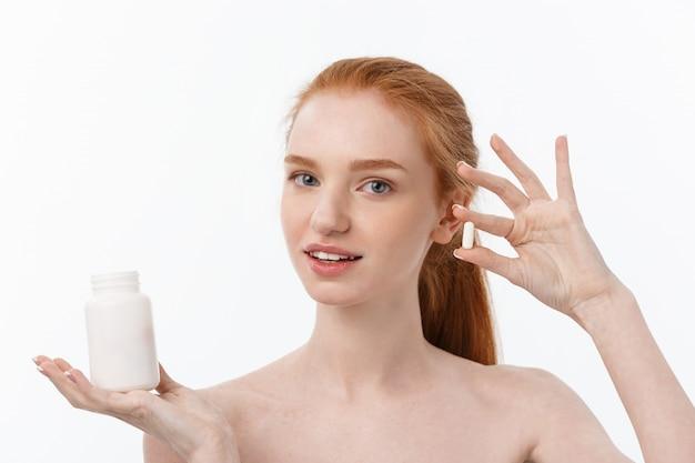 Retrato de mulher caucasiana jovem bonita segurando comprimidos, tentando cuidar do sistema imunológico e saúde sobre cinza