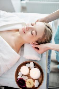 Retrato de mulher caucasiana loira fresca e bonita levando massagem de cabeça e rosto em salão de spa bem ...