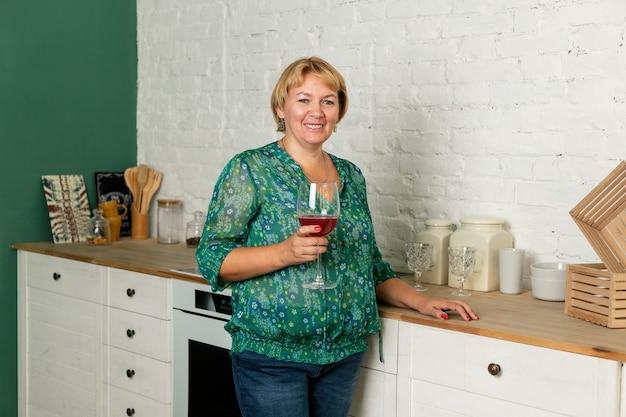 Retrato de mulher caucasiana sênior na cozinha moderna, segurando um copo de vinho, olhando para a câmera. estilo de vida de aposentadoria, passando tempo em casa.