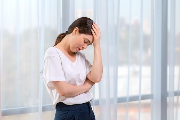 Retrato de mulher chorando, segurando sua cabeça com a mão. no fundo da janela. copie o espaço. o conceito de violência doméstica.