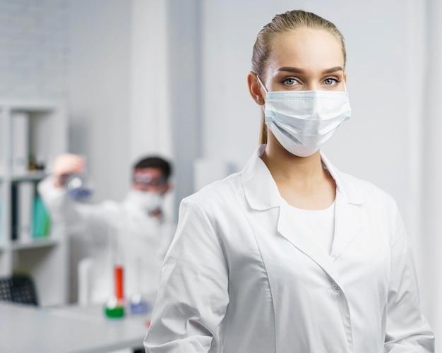 Retrato de mulher cientista no laboratório com máscara médica