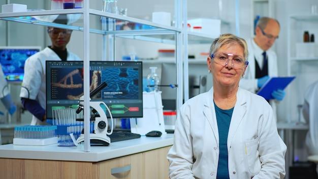 Retrato de mulher cientista sênior olhando para a câmera no moderno laboratório equipado. equipe multiétnica examinando a evolução do vírus usando ferramentas químicas e de alta tecnologia para pesquisa científica e desenvolvimento de vacinas