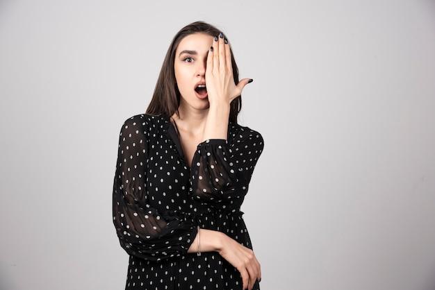 Retrato de mulher cobrindo um olho cinza.