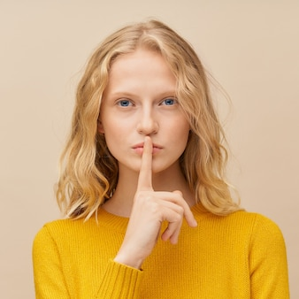 Retrato de mulher colocando o dedo nos lábios da cintura para cima, por favor, não faça barulho, silêncio, mantendo