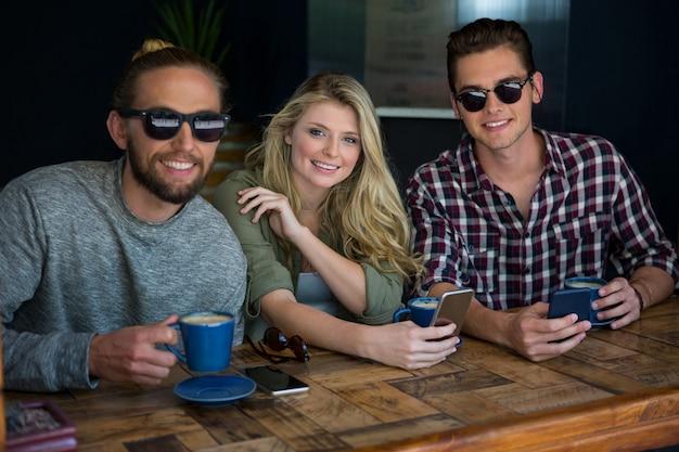 Retrato de mulher com amigos do sexo masculino usando óculos escuros em uma cafeteria