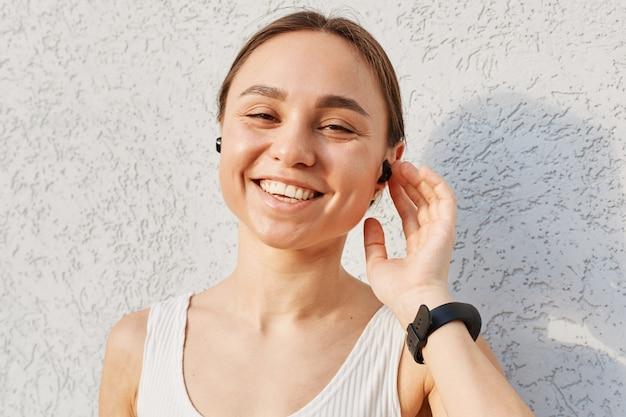 Retrato de mulher com aparência agradável, com sorriso dentuço, tocando airpods com a mão, olhando para a câmera, vestindo blusa branca, expressando positivo durante o treino ao ar livre.