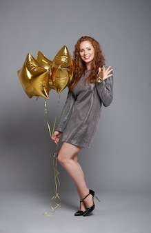 Retrato de mulher com balões e champanhe em estúdio tiro