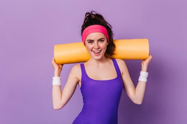 Retrato de mulher com bandana rosa para esportes e top roxo, posando com tapete de ioga na parede roxa