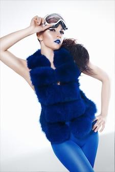 Retrato de mulher com batom azul em um colete de casaco de pele azul, leggings e ski mack