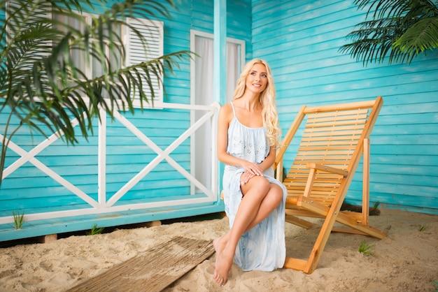 Retrato de mulher com blusa azul posando perto de casa de praia, superfície borrada na foto