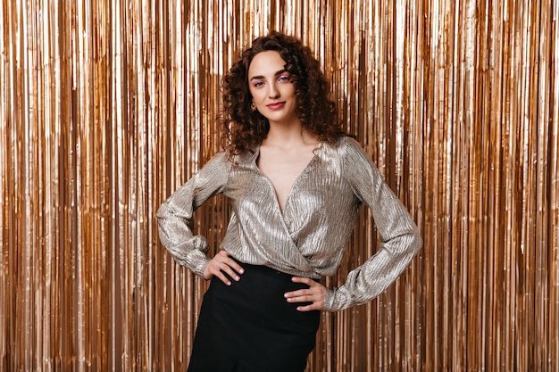 Retrato de mulher com blusa prateada posando em fundo brilhante