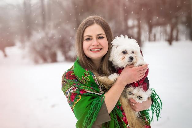 Retrato de mulher com cachorrinho branco em winter park
