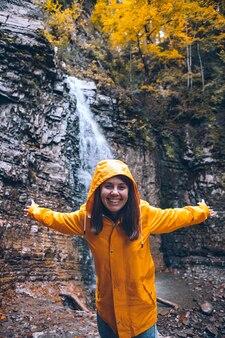 Retrato de mulher com capa de chuva amarela em frente ao conceito de caminhada na cachoeira de outono